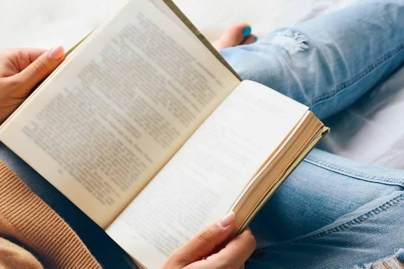 Una persona leyendo un libro recostada. EPDA.