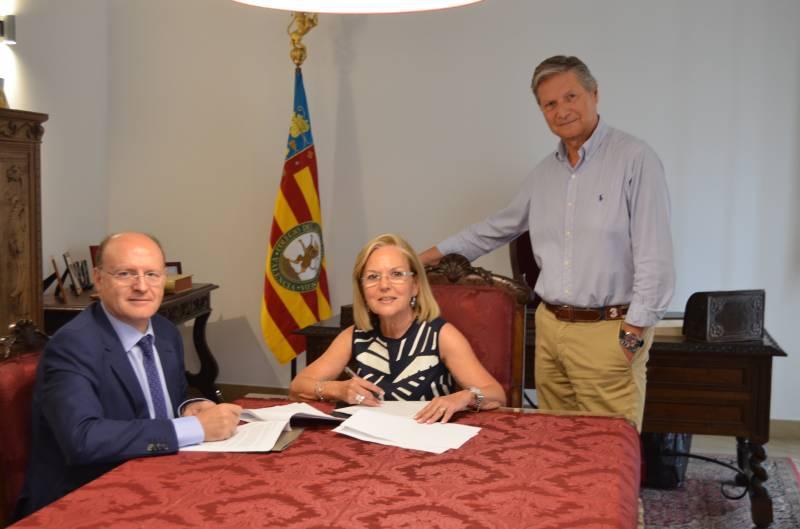 Juan Sabater y Amparo Fabra firman el convenio en presencia del Presidente del Colegio del Arte Mayor de la Seda