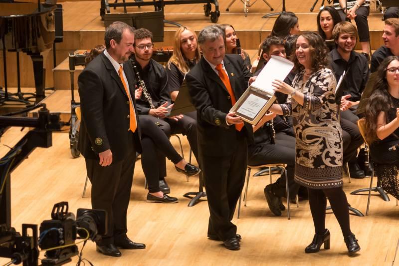La presidenta del Palau de la Música, Gloria Tello, entrega el guardó a la Societat Artístico Musical de Picassent