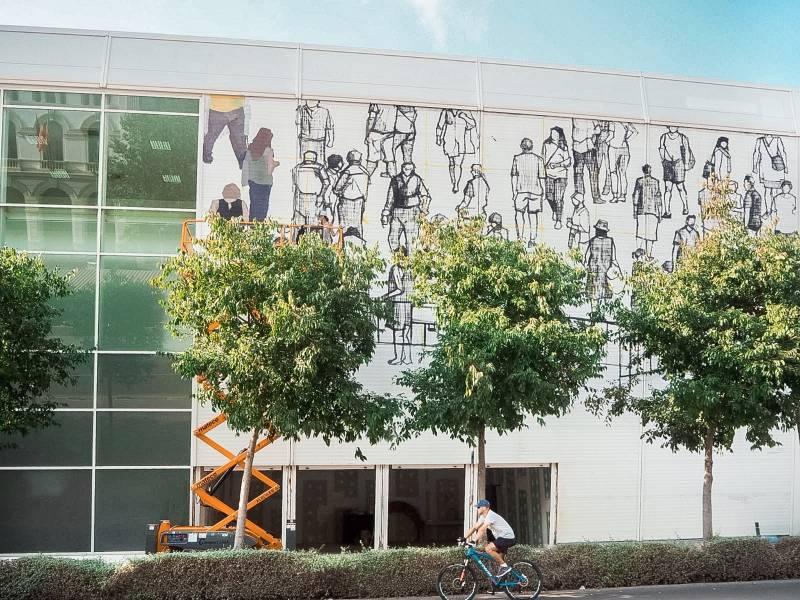 Fotografía de la intervención en fachada de La Base de la artista Hyuro, en pleno proceso.