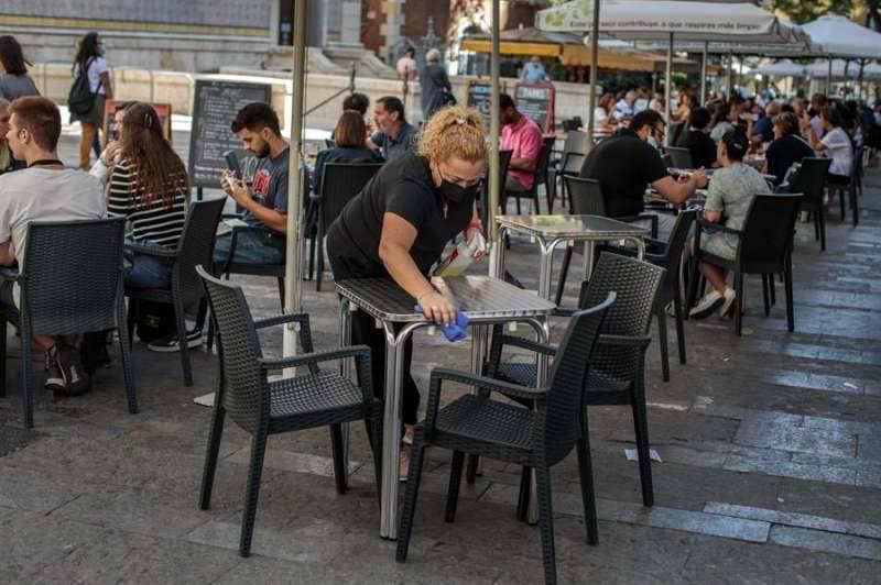 Una camarera limpia una mesa de una terraza./ EPDA