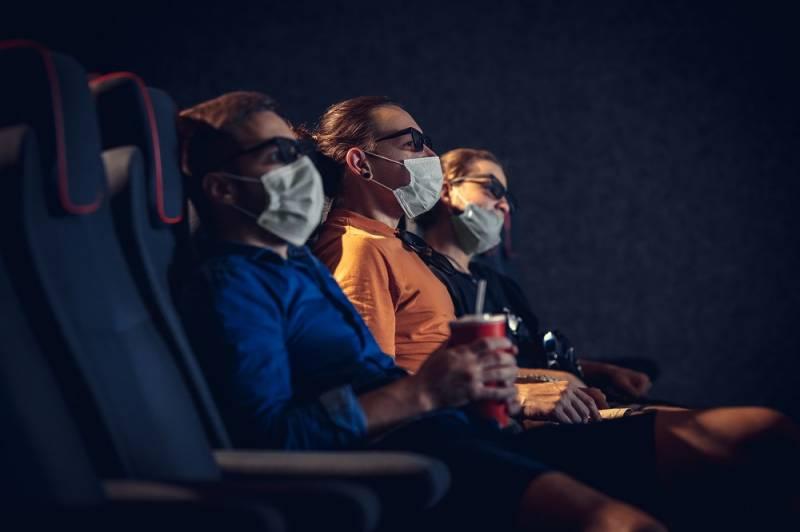 Personas en un cine con mascarilla. master1305. EPDA.