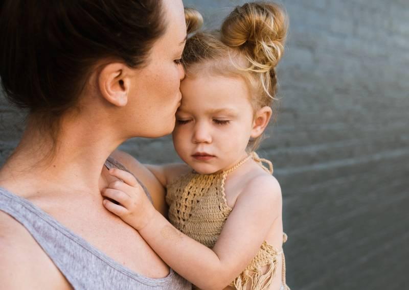 Una madre coge en brazos a su hija